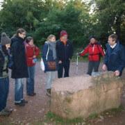 Referent mit Gruppe vor einem großen Stein