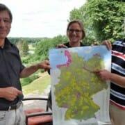 Guido Puhlmann (links), Dr. Elke Baranek und Michael Lammertz zeigen eine Karte mit den Nationalen Naturlandschaften in Deutschland. Dazu gehören 16 Nationalparks, 17 Biosphärenreservate, 104 Naturparks und das Wildnisgebiet Königsbrücker Heide in Sachsen. Foto: Andrea Schröder